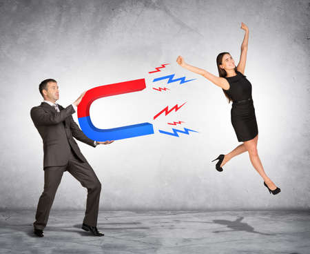 capturing: Concept of capturing people with marketing. Businessman attracting woman with magnet