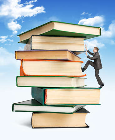 escalating: Pile of books with businessman climbing it on blue sky background