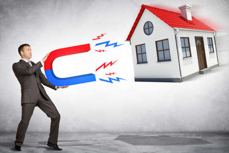 attracting: Businessman in suit holding big magnet attracting house Stock Photo