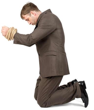 Junger Mann mit gefesselten Händen auf weißem Hintergrund kniend