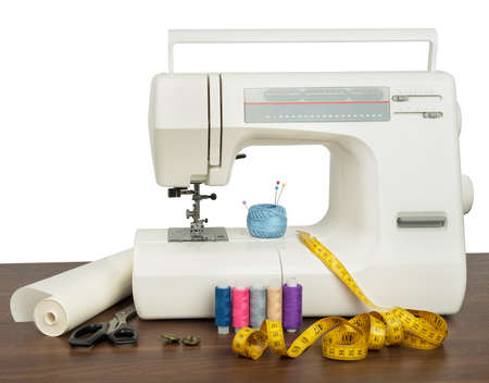stitchwork: Sewing machine and sewing accessories on wooden table. White background. Front view. Industry template for design