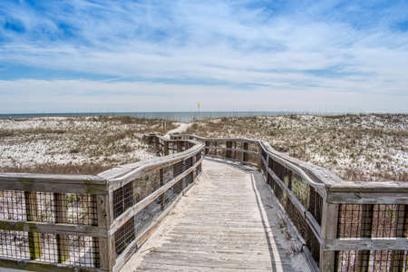 A very long boardwalk surrounded by shrubs in Perdido Key State Park, Florida Stock Photo