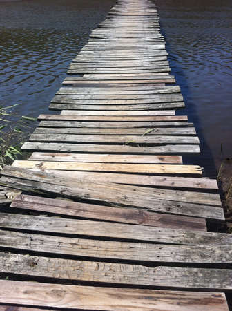 rickety: Rickety wooden bridge over river Stock Photo