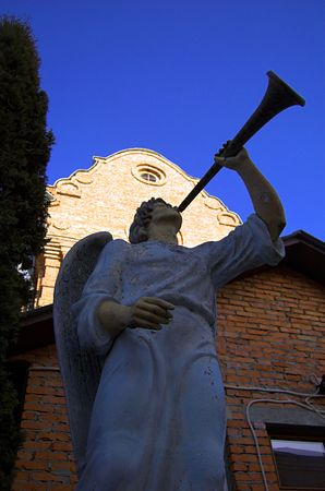 In a court yard of a church there is a statue of an angel with a pipe photo
