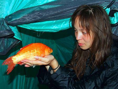 La ni�a tiene un pez de oro en las manos un crucian