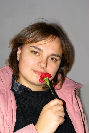 snění: The lovely girl poses with a red carnation