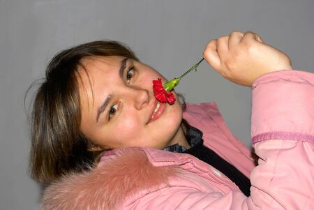 La encantadora ni�a posa con un clavel rojo  Foto de archivo