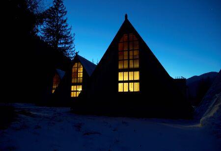 Cubiertas de nieve peque�as casas por la noche en las monta�as  Foto de archivo