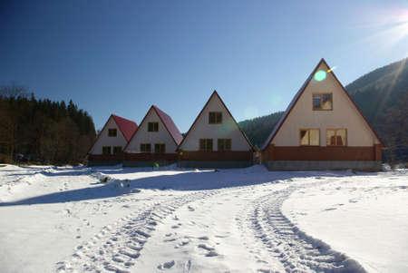 Soporte peque�o de cuatro casas en un glade solar Foto de archivo