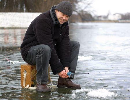 El hombre peces en el invierno por el hielo