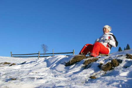 The sports girl on sledge climbs down a mountain Stock Photo - 2712561