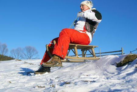 The sports girl on sledge climbs down a mountain Stock Photo - 2712562