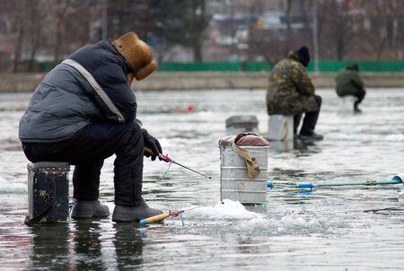 Tres hombres de pescado en hielo  Foto de archivo