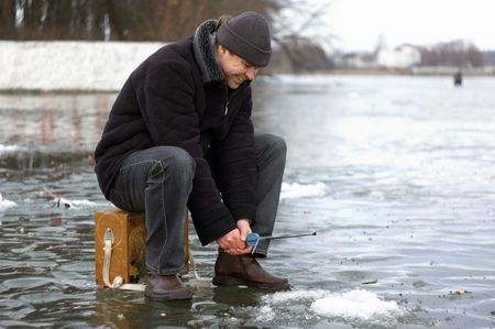 The man fishes in the winter on ice Stock Photo - 2736411
