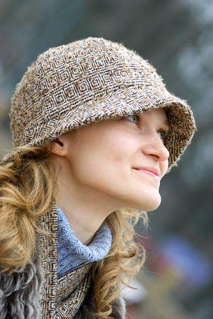 La muchacha hermosa en un casquillo mira hacia arriba