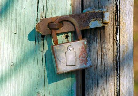 The old rusty lock hangs on a door photo