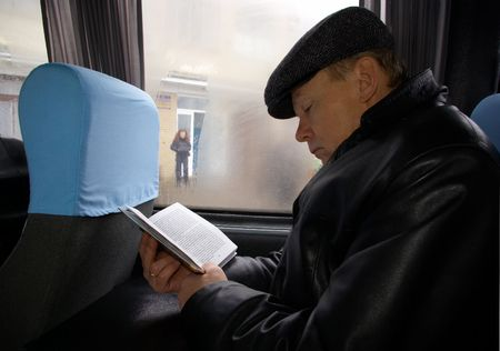 The man in the bus reads the book Standard-Bild