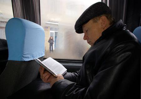 El hombre en el autob�s lee el libro  Foto de archivo