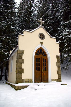 woodsy: Small chapel in a snow-covered wood