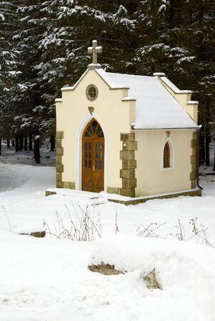 Peque�a capilla en un bosque de cubiertas de nieve