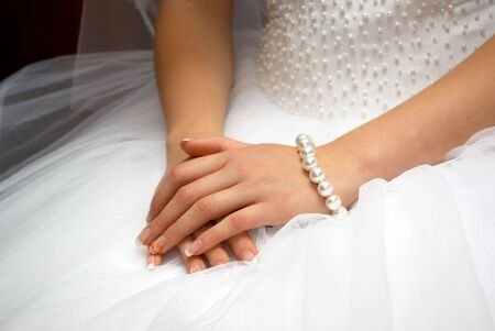 hands of fiancee are together on white dress Stock Photo