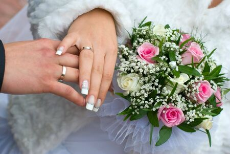 newly-weds hold a wedding bouquet in the hands