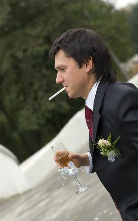 fiance: young man smokes a cigarette and drinks wine Stock Photo