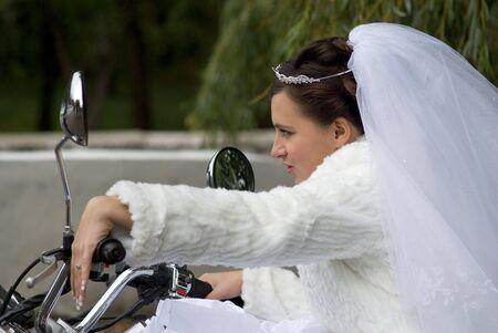 prometida en la ropa blanca y velo nupcial en un ciclo de motor