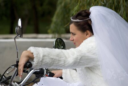 fiancee in white clothes and bridal veil on a motor cycle Standard-Bild