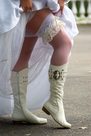 fiancee lifts clothes and shows the knee-boots Stock Photo