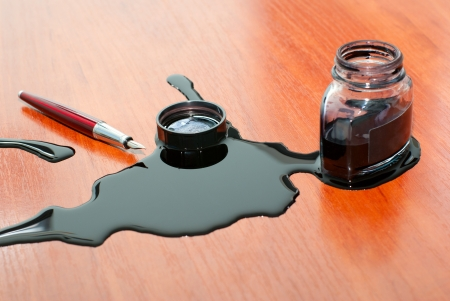 filthiness: black ink spill near red pen on  table