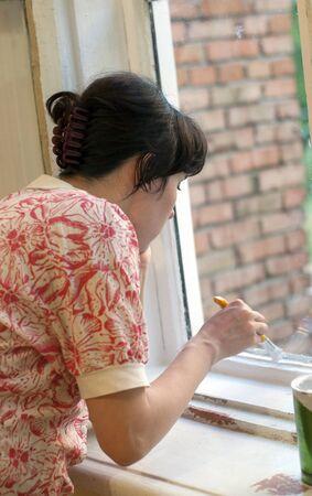 young woman paint wooden windowsill Standard-Bild