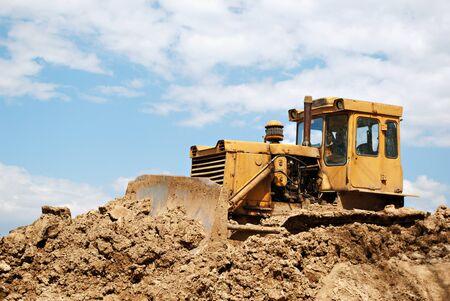 orange catterpillar tractor dig dirty ground Stock Photo