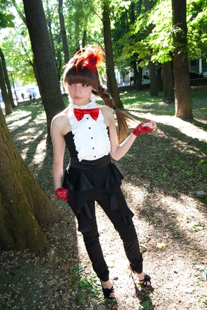 beautiful girl with red bow-tie cravat and cap in park photo