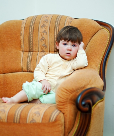 little baby girl sit in the armchair  Stock Photo