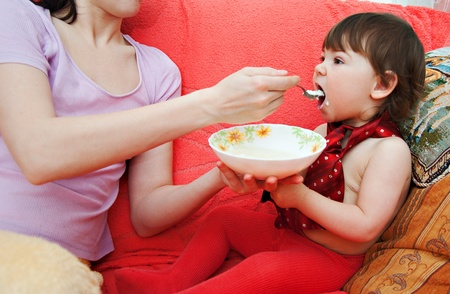 mother feed baby from plate