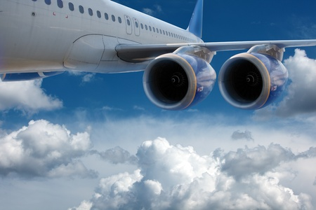 aircraft engine: Big airliner in the blue sky with clouds.