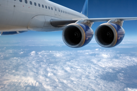 airplane wing: Big airliner in the blue sky with clouds.