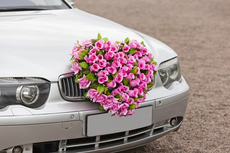 Beautiful red wedding bouquet on the car. photo