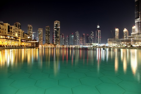 dubai mall: Modern night city of Dubai, with reflection on water surface. Stock Photo