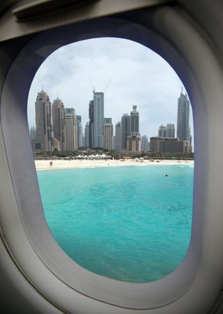 Blick aus dem Flugzeug-Fenster an einer schönen Bucht und der modernen Stadt.