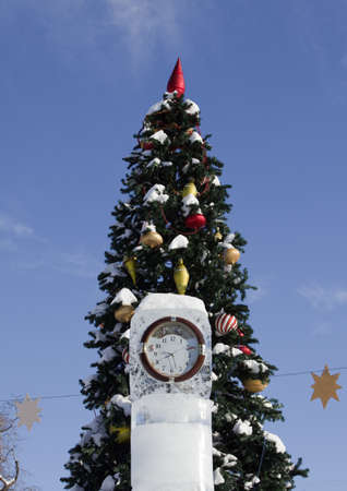 Clock in the ice pillar on the background of the Christmas tree. photo