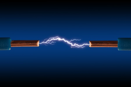 Electric cable with sparks on a black background. Stock Photo