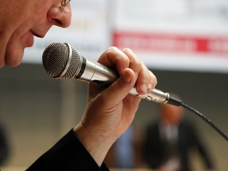 speaks: Image the announcer speaks into a microphone. Stock Photo