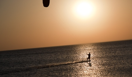professional kite surfer moves on water on a sunny summer day photo
