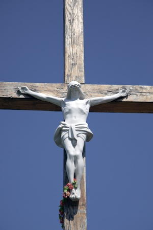 Stone statue of Jesus Christ crucified on a wooden cross on a blue background photo