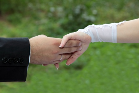 Bride and groom holding hands close up photo