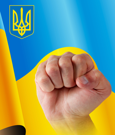 fist man on background of the flag and emblem of Ukraine photo