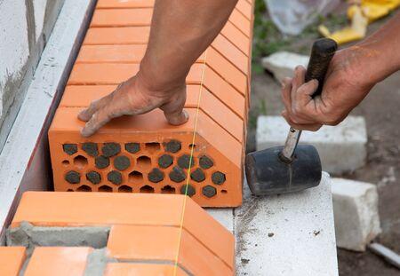 cement pile: Builder lays Bricks in cement mortar