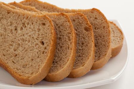pain: Tranches de pain brun sur une plaque Banque d'images